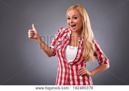 A beautiful young woman smiling and showing thumbs up in a plaid shirt