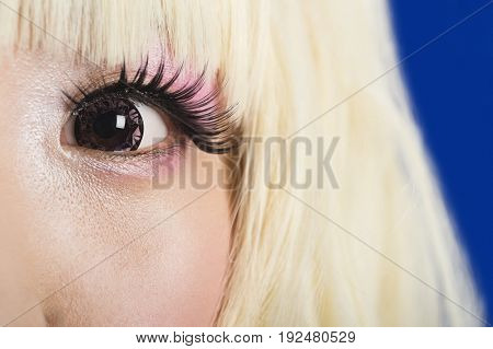 Close-up portrait of cute young woman's face with blond hair against blue background