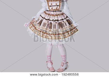 Low section of young woman in doll outfit standing over gray background