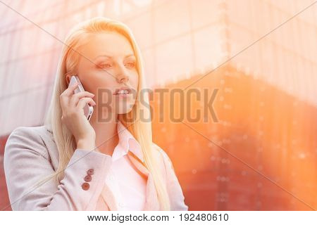 Close-up of blond businesswoman conversing on mobile phone with office building in background