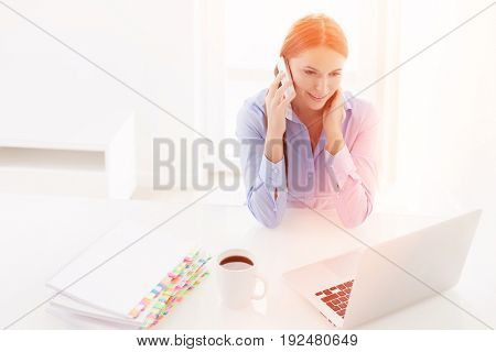 Woman using cell phone and looking at computer