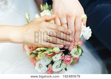 close-up of hands of the newlyweds at the wedding bouquet