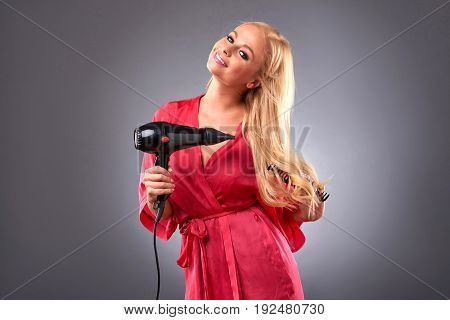A beautiful young woman wearing a pink robe and feeling happy while using a hairdryer and a hairbrush