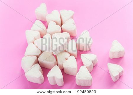 Marshmallows in heart shapes for Valentines day over pink paper background and ribbon to celebrate sweet love candy for couples