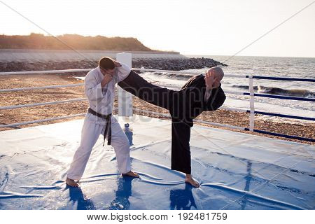 picture of Two professional karate fighters are fighting on the beach boxing ring
