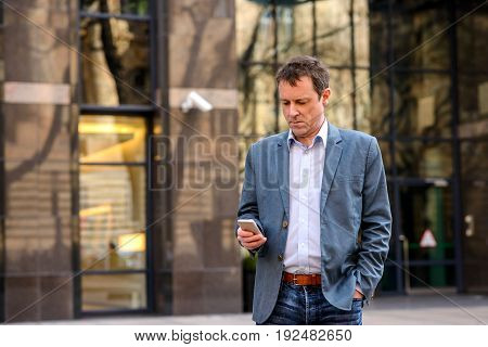 A middle age businessman standing in front of an office building while using his smartphone