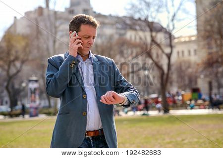 A middle age businessman standing in a park while talking on his phone and checking the time on his watch
