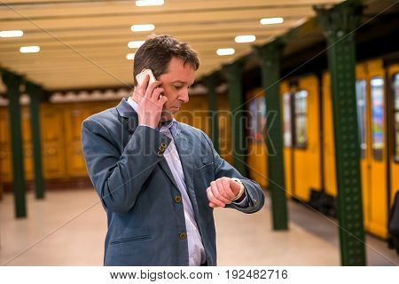 A middle age businessman standing and waiting in the subway while talking on his phone and checking his watch