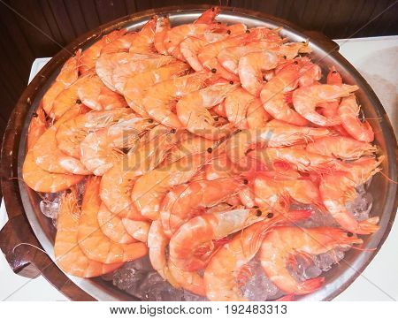 ​Big fresh cooked shrimps over ice tray in stainless steel pot for dinner