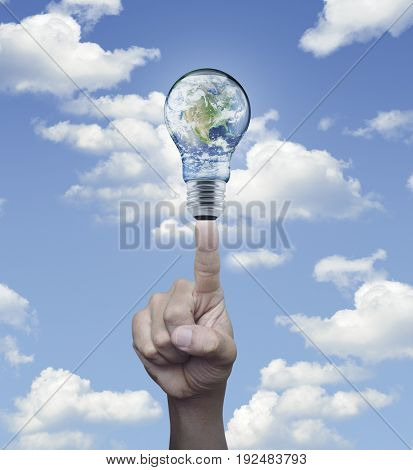 Hand pressing earth globe in light bulb over blue sky background Energy conservation and environmental concept Elements of this image furnished by NASA