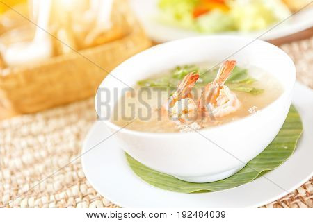 Traditional Thai porridge rice gruel and shrimp in white bowl with seasoning background on wood table.
