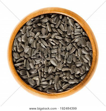 Sunflower seeds in wooden bowl. Fruits of the oilseed Helianthus Annuus, the common sunflower. Whole seeds with black hulls. Isolated macro food photo close up from above on white background.