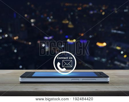 Telephone and mail icon button on modern smart phone screen on wooden table over blur colorful night light city tower Contact us concept
