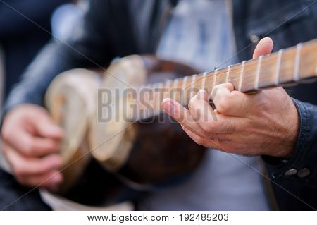 a man plays on a classical folk instrument tar of Azerbaijan