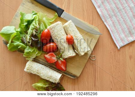bread roll and salad on wooden chop block