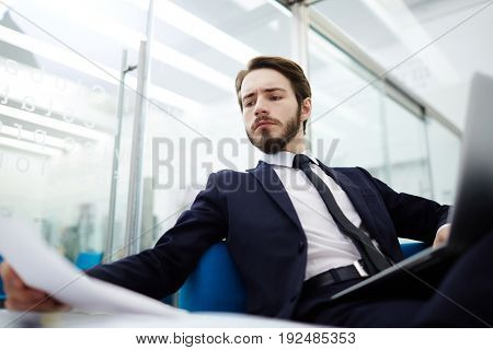 Young manager concentrating on reading financial papers