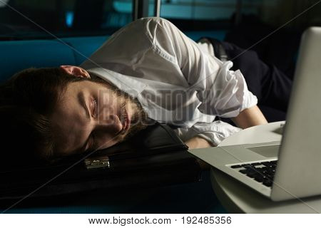Sleeping businessman spending night in office