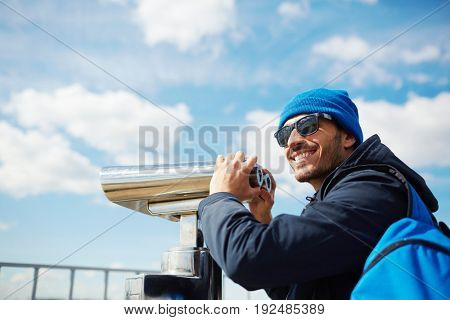 Young tourist in sunglasses observing surroundings