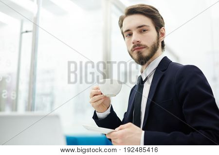 Young entrepreneur with cup of tea looking at camera at break