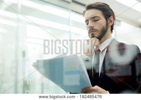 Young pensive man reading papers
