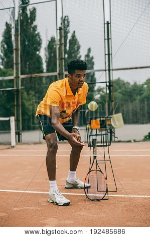Tennis player prepares to serve a tennis ball during a match. Young black man throws a ball on the tennis court.