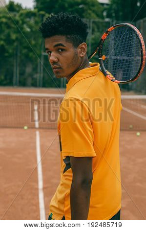 Handsome serious young man in polo shirt holding tennis racket on his shoulder and standing on tennis court.