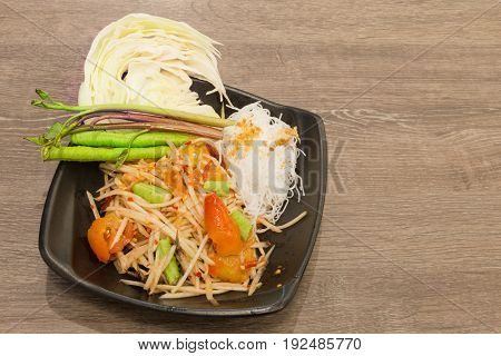 Spicy papaya salad (Som Tum) with salty crab serving with small rice noodles and fresh vegetables; long green beans cabbage and Thai morning glory in black plate over wooden table with copy space