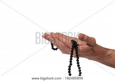 Muslim prayer. Hand of muslim man praying with rosary. Isolated on white background.