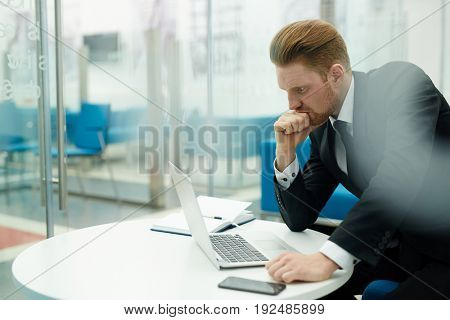 Concentrated salesman looking at laptop display in office