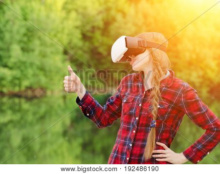 Girl shoots virtual reality glasses sunset in nature back view. Thumbs up