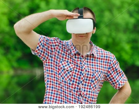 Man looks into the distance in the virtual reality glasses on background of green forest