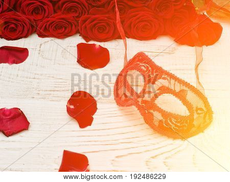 Red carnival mask lies on a white wooden table surrounded by petals and a bouquet of roses