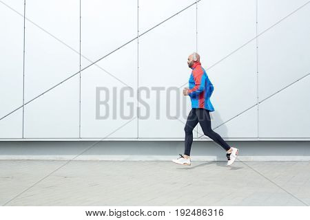 Young runner moving along wall