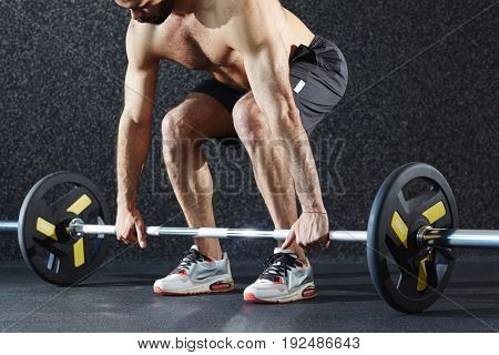Muscular man making effort while lifting heavy weight from the floor