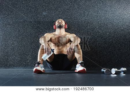 Young athlete leaning against wall while sitting on the floor and listening to music in headphones