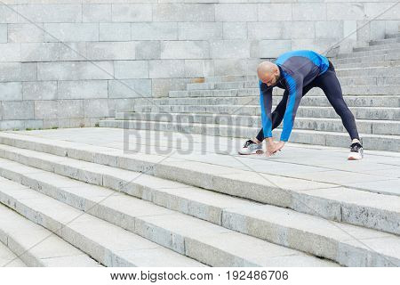 Acrtive young man doing stretching exercise