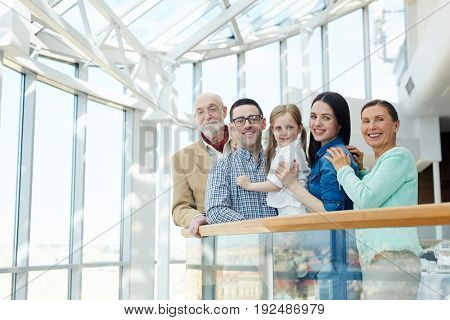 Happy big family of little girl, young and senior couples looking at camera