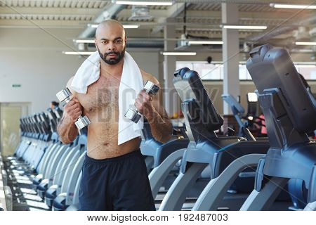 Shirtles man with towesl and dumbbells exercising on background of treadmills