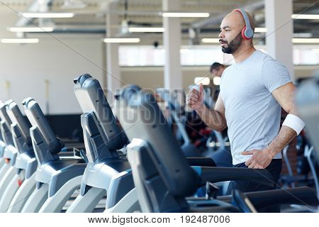 Young sportsman running on treadmill