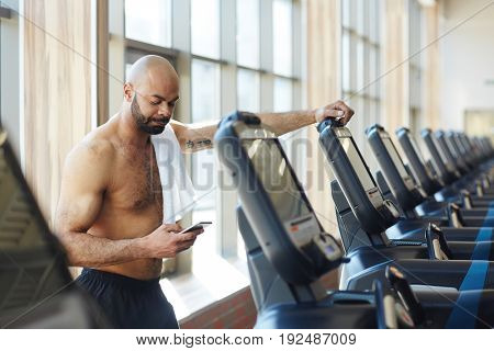 Young sporty man leaning on treadmill and texting in smartphone