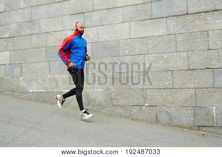Young sprinter with headphones running along wall