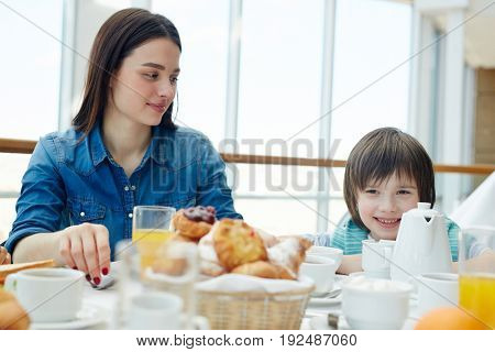 Happy boy and young woman eating breakfast
