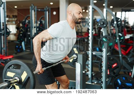 Strong man lifting weight in gym