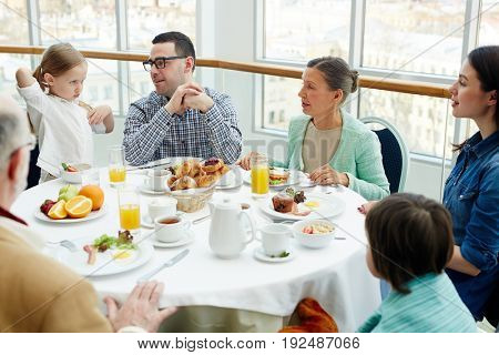 Big family having talk by breakfast in restaurant