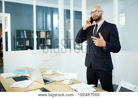 Confident business leader speaking to client or manager on cellphone