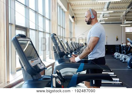 Active young man training on treadmill