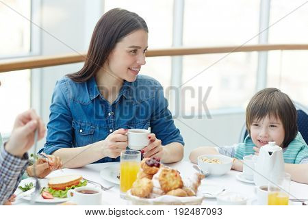 Happy young woman and her son dining in restaurant
