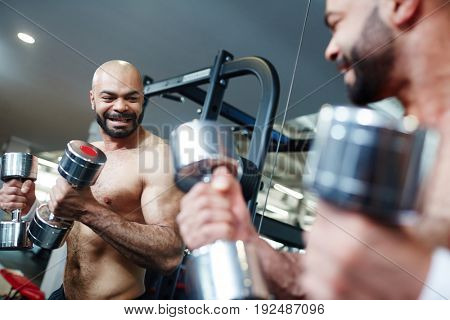 Active man looking in mirror while exercising with dumbbells