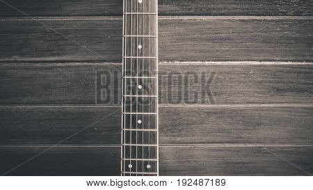 ooden guitar. Close-up of guitar lying on vintage wood background