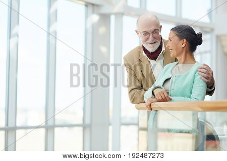 Aged couple leaning against railings and talking